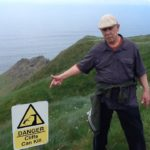 Don pointing at a warning sign at the Cliffs of Moher